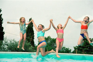 girls jumping in a pool